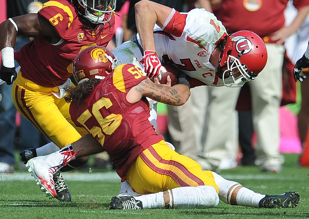 . Southern California linebacker Anthony Sarao (56) tackles Utah quarterback Travis Wilson (7) during the first half of an NCAA college football game in the Los Angeles Memorial Coliseum in Los Angeles, on Saturday, Oct. 26, 2013.  (Photo by Keith Birmingham/Pasadena Star-News)