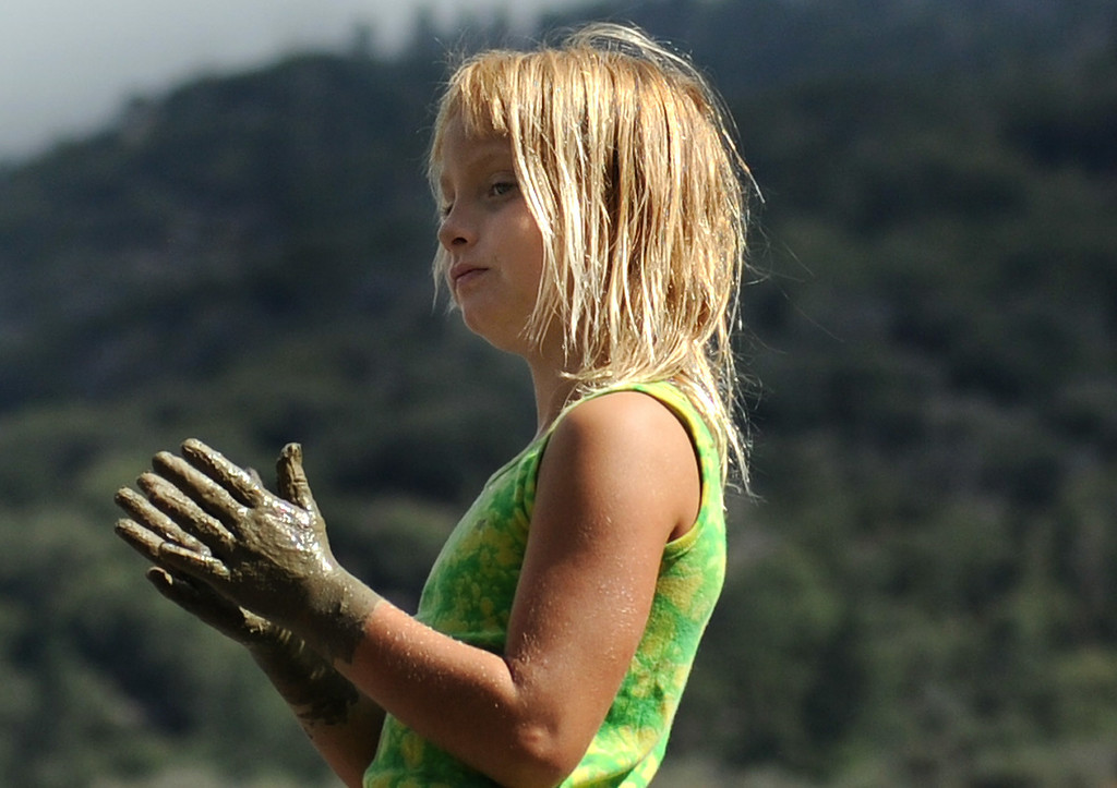 . Shayla Middleton, 8, of Forest Falls, plays in the mud as clean up crews continue efforts to open Valley of the Falls Drive on Monday, August 4, 2014 in Forest Falls, Ca. (Micah Escamilla/San Bernardino Sun)