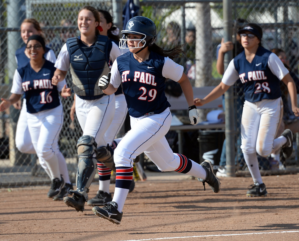 . St. Paul\'s Lovie Lopez (#29) is chased by teammates as she crosses home plate after hitting a three-run homerun as they play Bishop Amat in their Del Rey League girls softball game at York Field in Whittier on Thursday March 27, 2014. St. Paul defeated Bishop Amat 7-5. (Staff Photo by Keith Durflinger/Whittier Daily News)