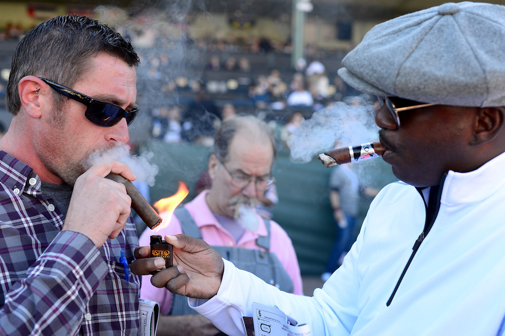 . Eric Williams, right, of Chicago, helps out Jeremiah Johnson, of Nebraska, with his cigar during the Breeders\' Cup at Santa Anita Park in Arcadia Friday, November 1, 2013. (Photo by Sarah Reingewirtz/Pasadena Star-News)