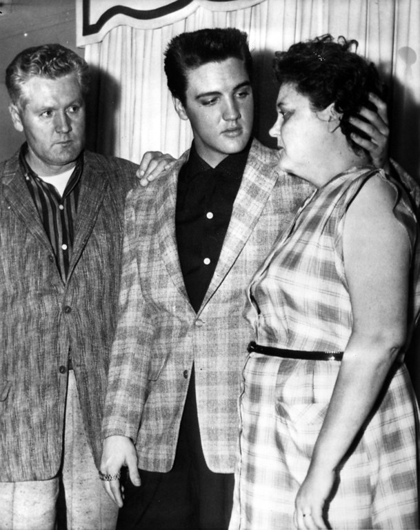 . Elvis Presley, 23-year-old rock and roll singer and movie actor, comforts his mother Gladys as his father, Vernon E., looks on. The scene took place when photographers were admitted to the Presleys\' Memphis home on the eve of Elvis\' induction into the army. (AP-Photo/fg/stf/fg) 23.03.1958