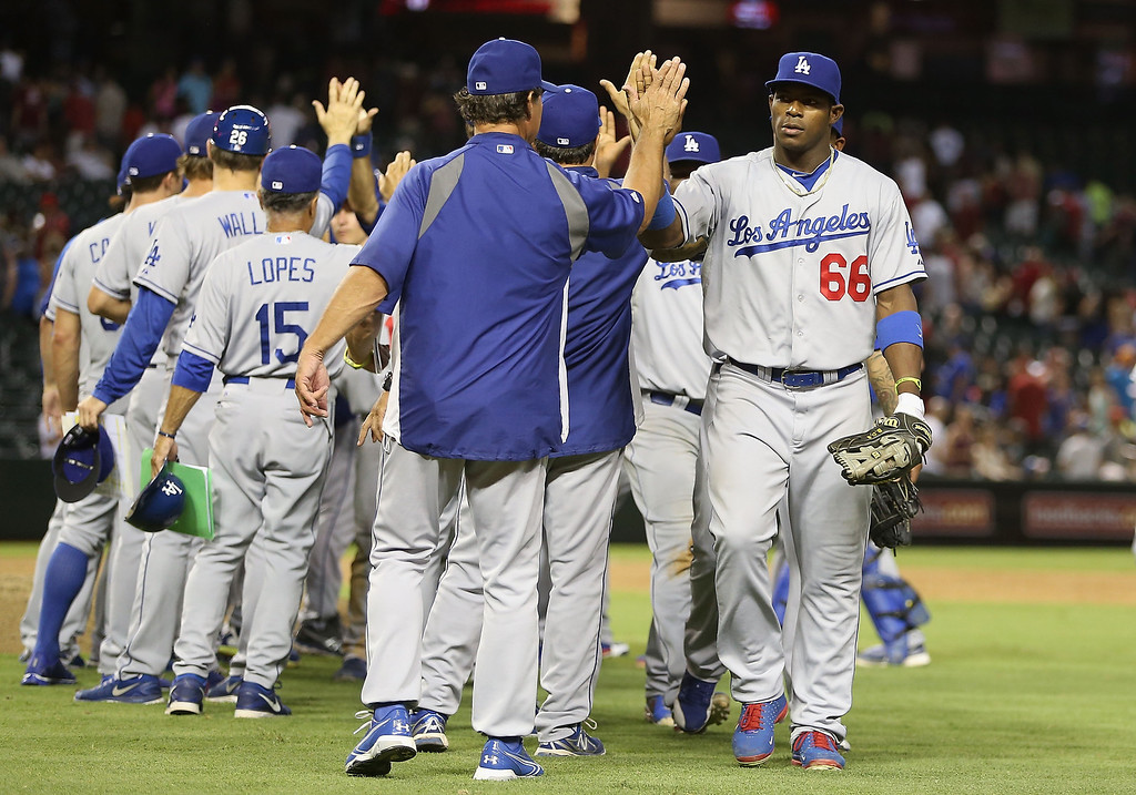 . PHOENIX, AZ - JULY 08:  Yasiel Puig #66 of the Los Angeles Dodgers high fives manager Don Mattingly after defeating the Arizona Diamondbacks in the MLB game at Chase Field on July 8, 2013 in Phoenix, Arizona. The Dodgers defeated the Diamondbacks 6-1. (Photo by Christian Petersen/Getty Images)