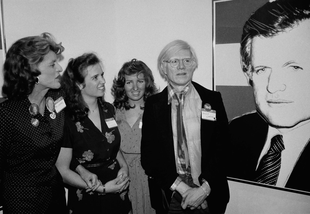 . Artist Andy Warhol, right, stands next to a poster in red, white and blue of Senator Edward Kennedy that he created to help launch a nationwide fund raising campaign for the senator at an opening at the Brewster gallery on Monday, March 3, 1980 in New York.  The posters, produced in a limited edition, will be sold through Kennedy for President headquarters throughout the nation.   With Warhol are, from left: Patricia Kennedy Lawford, with her nieces Kerry and Courtney, daughters of the late Sen. Robert Kennedy. (AP Photo/Rick Booklet)