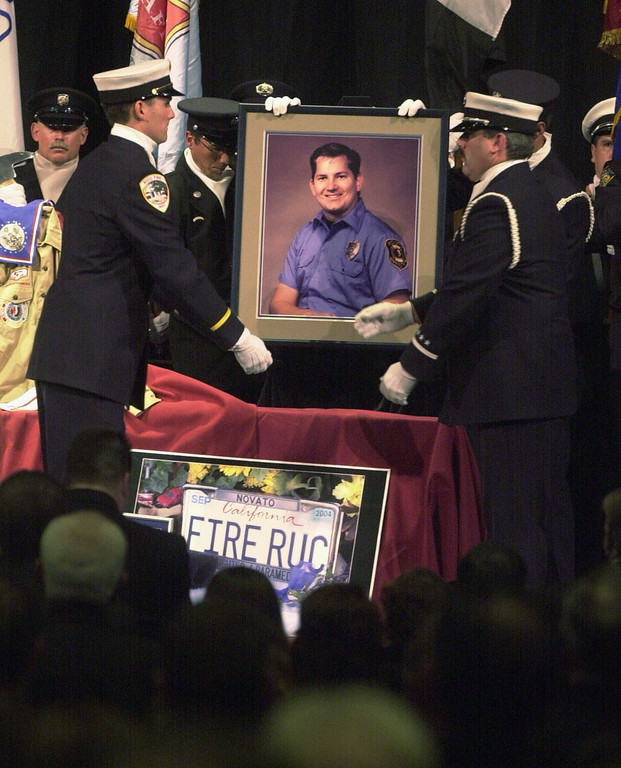 . SAN RAFAEL, CA - NOVEMBER 12:  Members of an honor guard place a photograph of Novato California firefighter Steven Rucker alongside his personal effects collected on the stage at his memorial service at the Marin Veterans Memorial Auditorium November 12, 2003 in San Rafael, California. Rucker was killed while fighting the Cedar Fire in San Diego County October 29, 2003.  (Photo by Robert Tong-Pool/Getty Images)