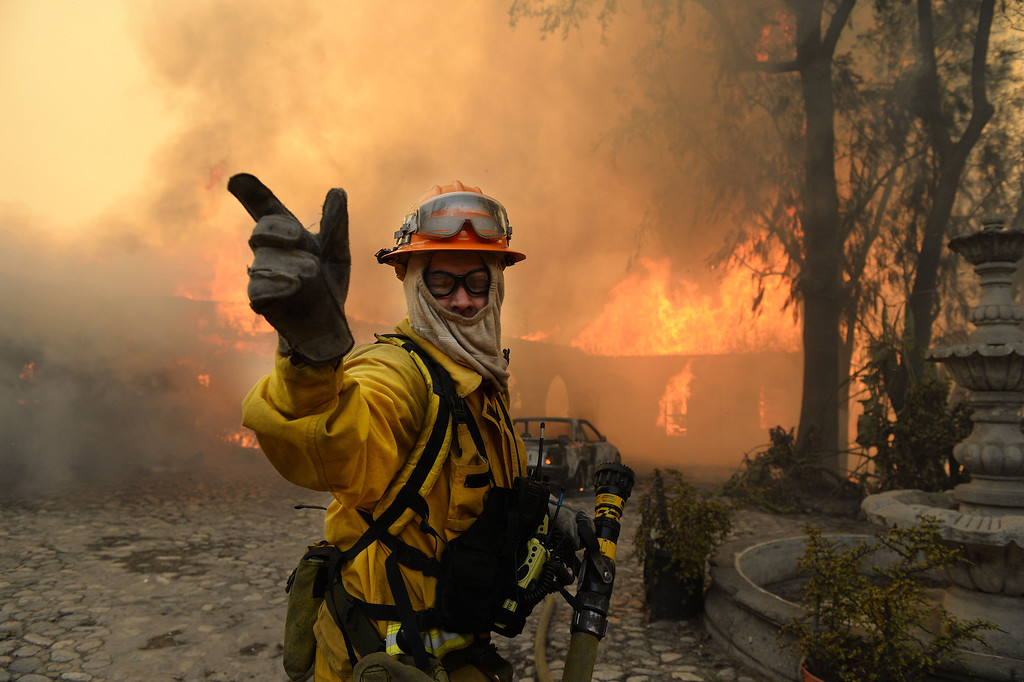 . A fireman calls for more water on the burning Singer home above Glendora. The Colby Fire burns above Glendora Thursday January 16, 2014. A portion of the former Singer home, of sewing machine fame, partially burned. (Will Lester/Inland Valley Daily Bulletin)