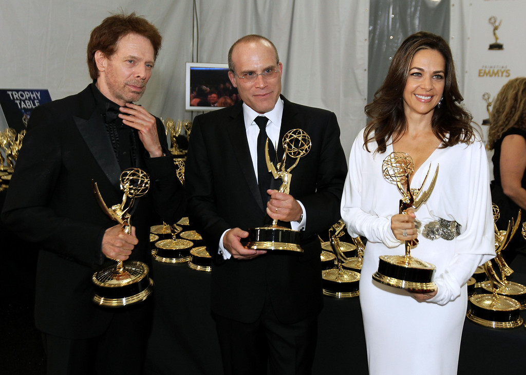 """. Producer Jerry Bruckheimer, from left, Jonathan Littman and Elise Doganieri, winners of the Outstanding Reality-Competition Program for \""""The Amazing Race\"""", poses backstage at the 64th Primetime Emmy Awards at the Nokia Theatre on Sunday, Sept. 23, 2012, in Los Angeles. (Photo by Matt Sayles/Invision/AP)"""