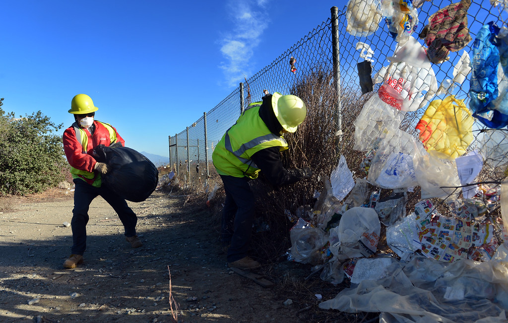 . Workers from Athens Service pull wind blown trash Monday December 9, 2013, from a fence bordering the 210 freeway in Fontana. Trash was stuck along nearly a mile of fence line. (Staff photo by Rick Sforza/The Sun)