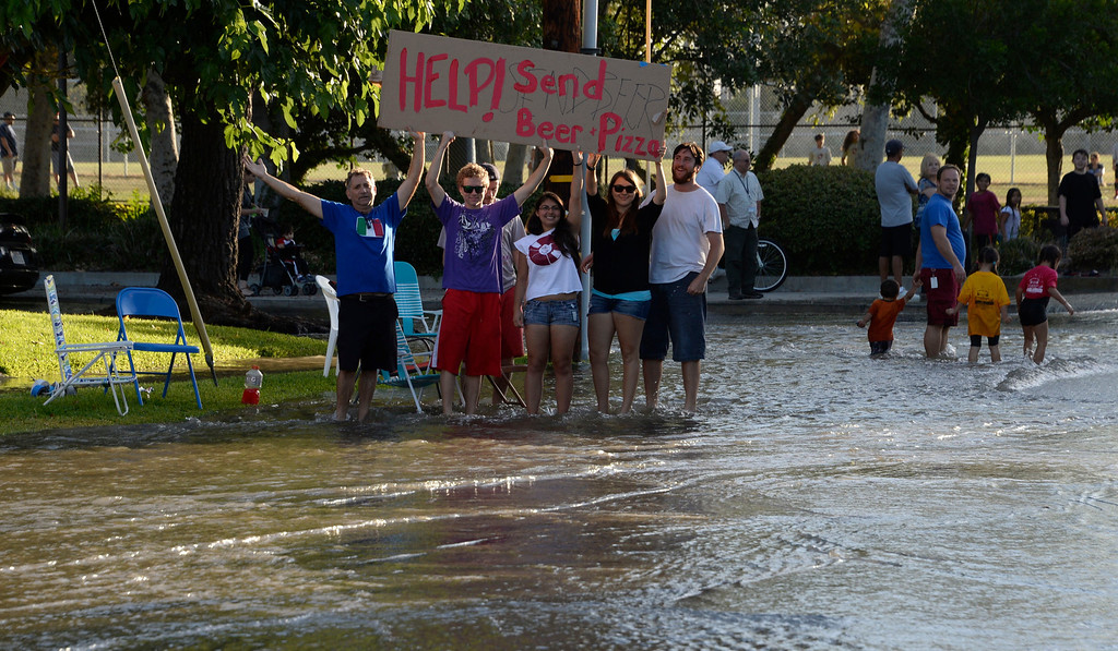 . June 17,2014. Burbank. CA. Teens have fun with a sign asking for Beer and Pizza after a 30 inch water main broke at the Burbank Fire training center Tuesday. The water created a river in the streets that were near by the brake but did not flood any homes near by. Burbank water and power crews are on scene working to shut off the water.  Photo by Gene Blevins/LA DailyNews