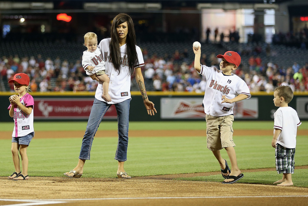 . PHOENIX, AZ - JULY 08:  (L-R) Shiloh, Julianne Ashcraft, wife to fallen firefighter Andrew Ashcraft, Ryder and Tate Andrew throw out the Ceremonial first pitch before the MLB game between the Arizona Diamondbacks and the Los Angeles Dodgers at Chase Field on July 8, 2013 in Phoenix, Arizona.  The Arizona Diamondbacks are honoring the 19 Granite Mountain Interagency Hotshot Crew firefighters who died battling a fast-moving wildfire near Yarnell, AZ.  (Photo by Christian Petersen/Getty Images)