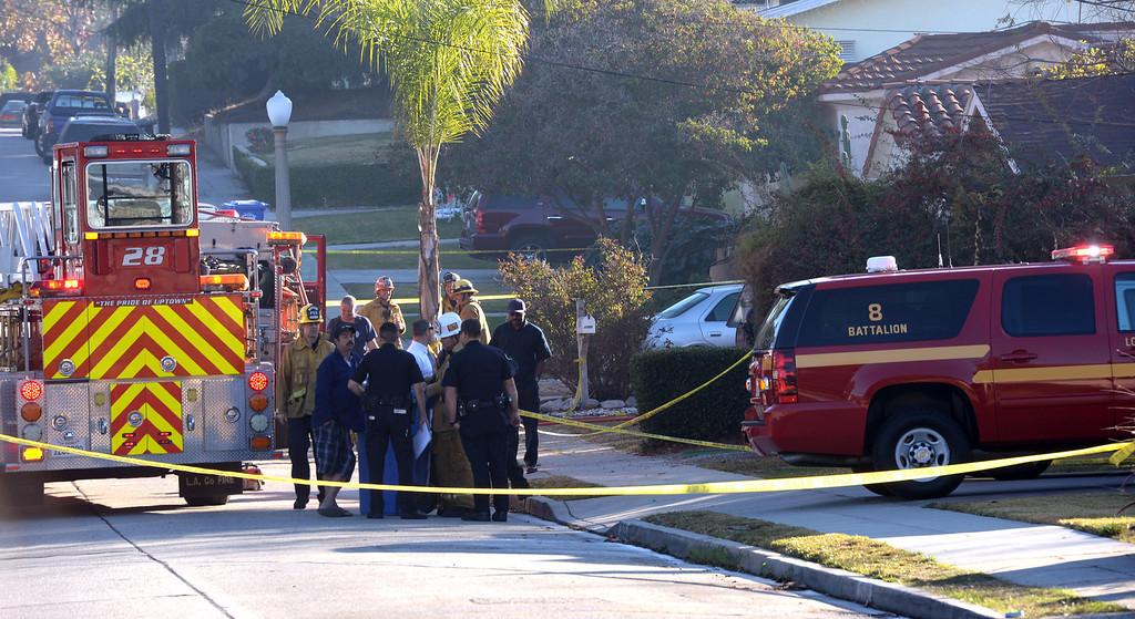 . Los Angeles County Firefighters and Whittier Police officers investigate a house fire on the 13500-block of Via Del Palma in Whittier Where two residents were found dead inside on Thursday January 2, 2014. (Staff Photo by Keith Durflinger/Whittier Daily News)