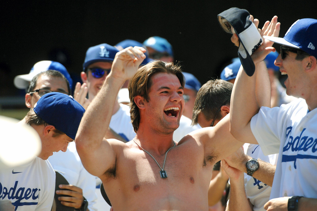 . A fan celebrates catching a foul ball with his hat. Saturday, August 10, 2013, at Dodger Stadium. (Michael Owen Baker/L.A. Daily News)