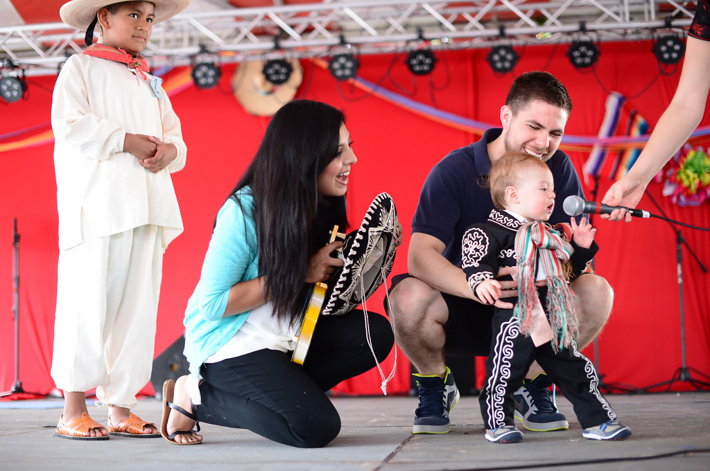 . Landon Herrera, 11 months, of San Gabriel, answers questions with the help of mom Danielle Diaz-Infante and dad Blain during a children\'s costume contest in the 242nd Annual La Fiesta de San Gabriel Saturday, August 31, 2013 at the San Gabriel Mission. Landon was the third generation in the Herrera family to wear the Charro costume. Jorge Ruiz, 8, of San Gabriel, is wearing a Oaxacan outfit. The fiesta runs through Sunday. (Photo by Sarah Reingewirtz/Pasadena Star-News)