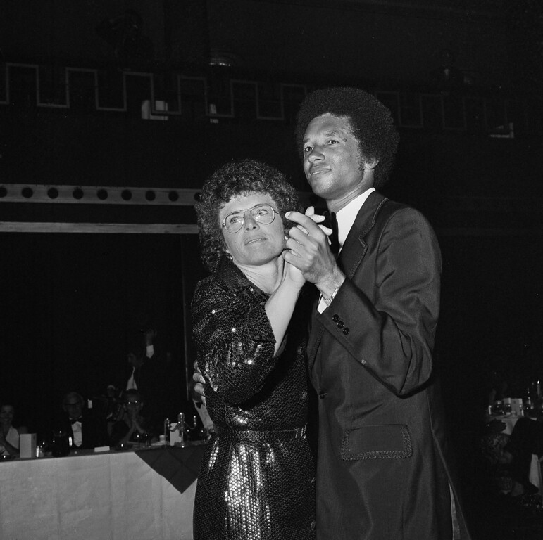 . Arthur Ashe of Richmond, Va., the first black tennis player to win the men\'s singles title at Wimbledon, takes the dance floor with Billie Jean King of San Mateo, Calif., the women\'s title holder at the British Lawn Tennis Associaiton ball at Grosvenor House in London, July 5, 1975.  (AP Photo/Smith)