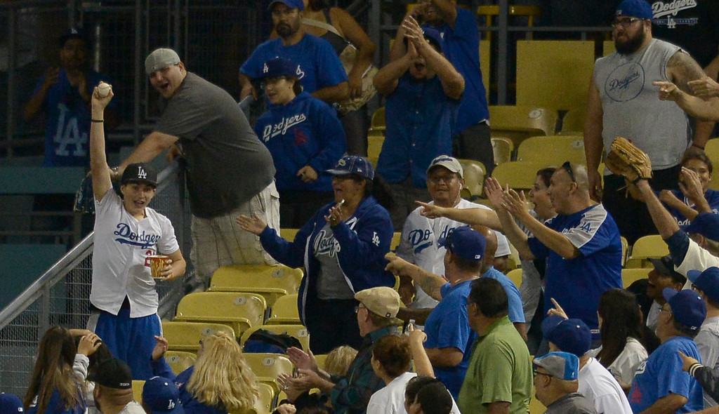. A fan holds up a ball that bounced into the stands off the bat of Adrian Gonzalez, and was ruled a ground rule double in the 3rd inning. The Dodgers played the San Diego Padres at Dodger Stadium. Los Angeles, CA. 8/20/2014(Photo by John McCoy Daily News)