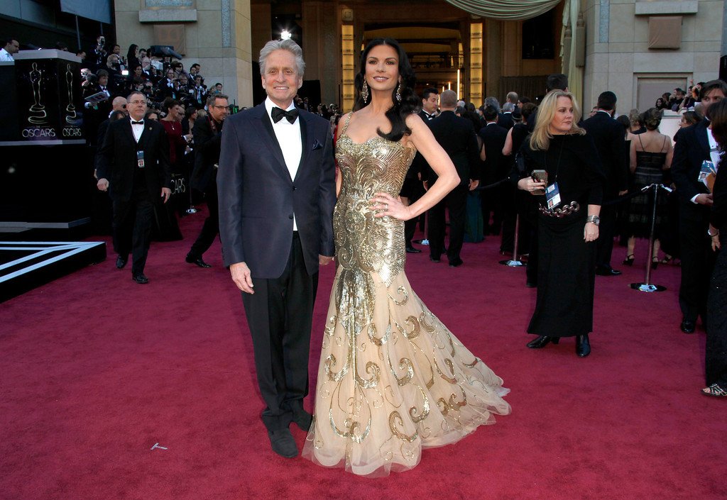 . FILE - In this Feb. 24, 2013 file photo, actors Michael Douglas, left, and Catherine Zeta-Jones arrive at the Oscars at the Dolby Theatre, in Los Angeles. According to her publicist on Monday, April 29, 2013, Zeta-Jones has pro-actively checked into a health care facility. Previously, she has said that she is committed to periodic care in order to manage her health in an optimum manner. (Photo by Carlo Allegri/Invision/AP, File)