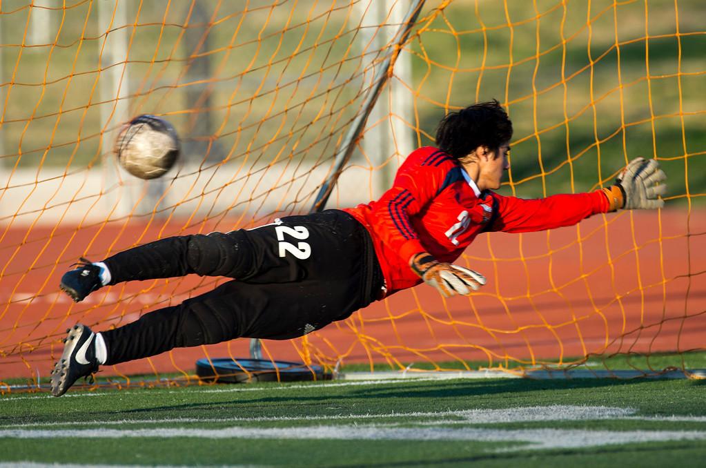 . South Pasadena goal keeper Kevin Foster (22) dives to block a goal from Monrovia\'s Joel Cortez (21) in the second half of Boys soccer, South Pasadena at Monrovia on Wednesday, Jan. 8, 2013. Monrovia won 5-1. (Photo by Watchara Phomicinda/ Pasadena Star-News)