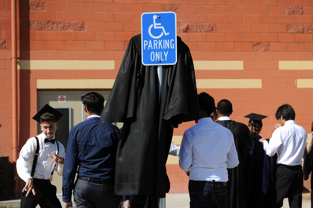 . A gown hangs from a parking sign as graduates gather at Cesar Chavez Learning Academies Social Justice Humanitas Academy in San Fernando, Wednesday, June 5, 2013. (Michael Owen Baker/Staff Photographer)