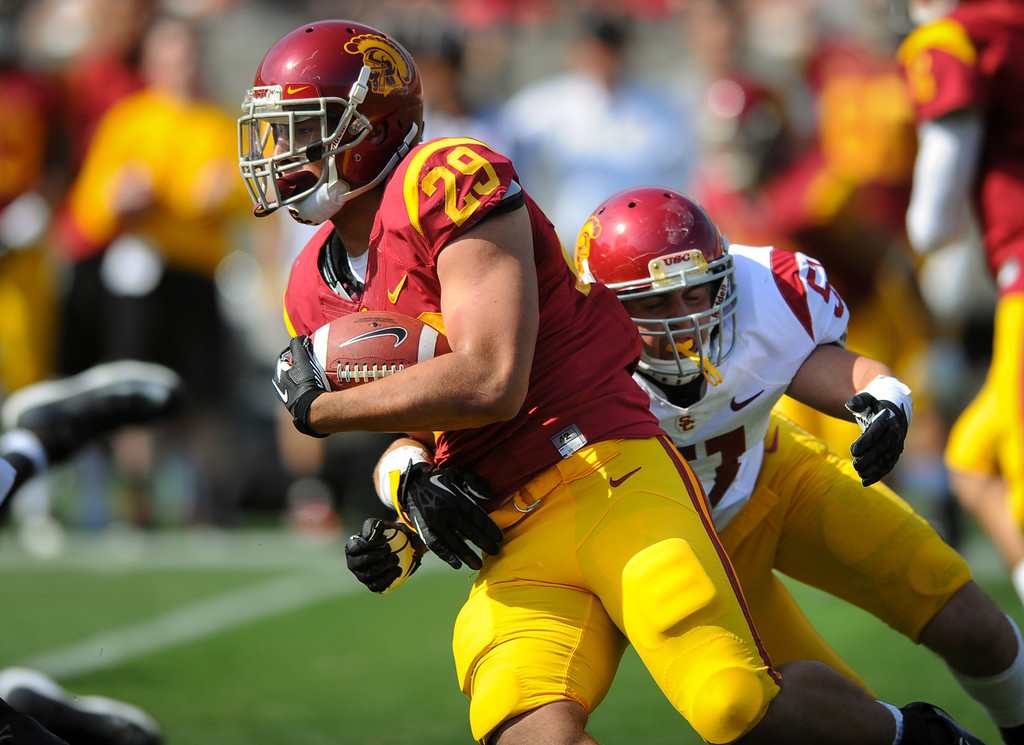 . USC RB Ty Isaac slips past LB Joel Foy in the backfield at the spring game. (Photo by Michael Owen Baker/L.A. Daily News)