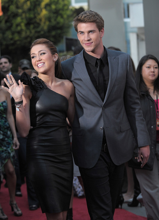 """. LOS ANGELES, CA - MARCH 25:  Actress Miley Cyrus and actor Liam Hemsworth arrive at \""""The Last Song\"""" at The Arclight on March 25, 2010 in Los Angeles, California.  (Photo by Jordan Strauss/Invision/AP Images)"""