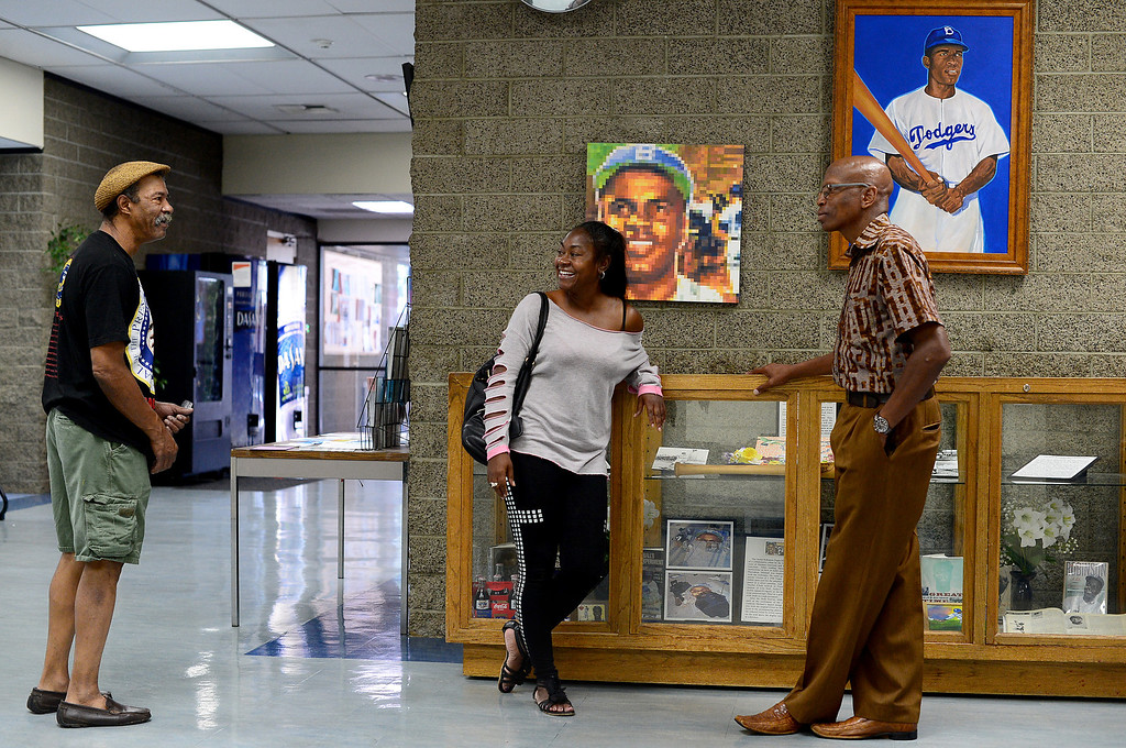 ". ""Extremely disheartening,\"" says Jarvis Emerson, manager of the Jackie Robinson Community Center in Pasadena, of the defacement of the Jackie Robinson statue in New York City. Emerson, right, gives landlord advice to Kimberlisa Best, of Altadena, in the lobby of the Jackie Robinson Community Center Thursday, August 15, 2013. (Photo by Sarah Reingewirtz/Pasadena Star-News)"