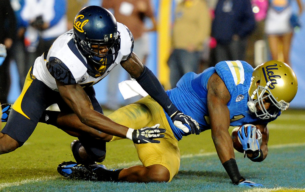 . UCLA wide receiver Shaquelle Evans (1) catches a pass for a 22 yard touchdown past California defensive back Isaac Lapite (20) during the second half of their college football game in the Rose Bowl in Pasadena, Calif., on Saturday, Oct. 12, 2013.   (Keith Birmingham Pasadena Star-News)