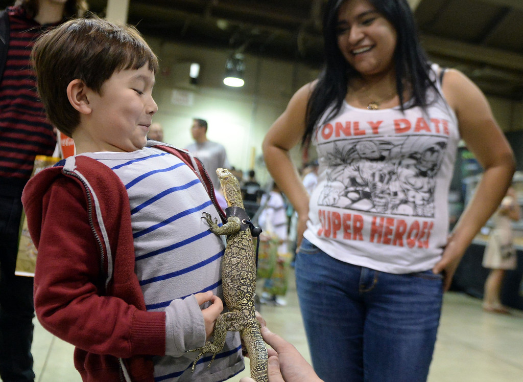 ". Six year-old Zac Wu of La Canada watches as ""Dexter\"" the Quince monitor lizard crawls up his chest as Elizabeth Corona of Camarillo looks on during the Reptile Super Show which is the world\'s largest reptile show with more than 500 tables of rare & unique animals including lizards, turtles, frogs, supplies at the Fairplex in Pomona, Calif., on Saturday, Jan.4, 2014.   (Keith Birmingham Pasadena Star-News)"