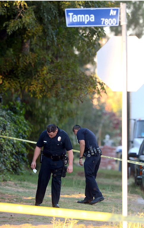 . LAPD officers search for evidence near the scene of a shootout with robbery suspects who engaged officers in a pursuit, shootout and manhunt in Reseda, Ca July 8, 2013.  Both suspects were apprehended after hours of searching along Tampa Ave near Strathern St. Monday evening.(Andy Holzman/Los Angeles Daily News)