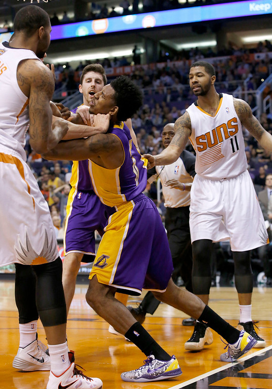 . Los Angeles Lakers\' Nick Young, second from right, gets into a scuffle with Phoenix Suns\' Marcus Morris, left, and other Suns players, as Suns\' Markieff Morris (11) and Lakers\' Ryan Kelly, second from left, arrive for the fracas during the first half of an NBA basketball game Wednesday, Jan. 15, 2014, in Phoenix. Young and Suns\' Alex Len were both ejected from the game. (AP Photo/Ross D. Franklin)