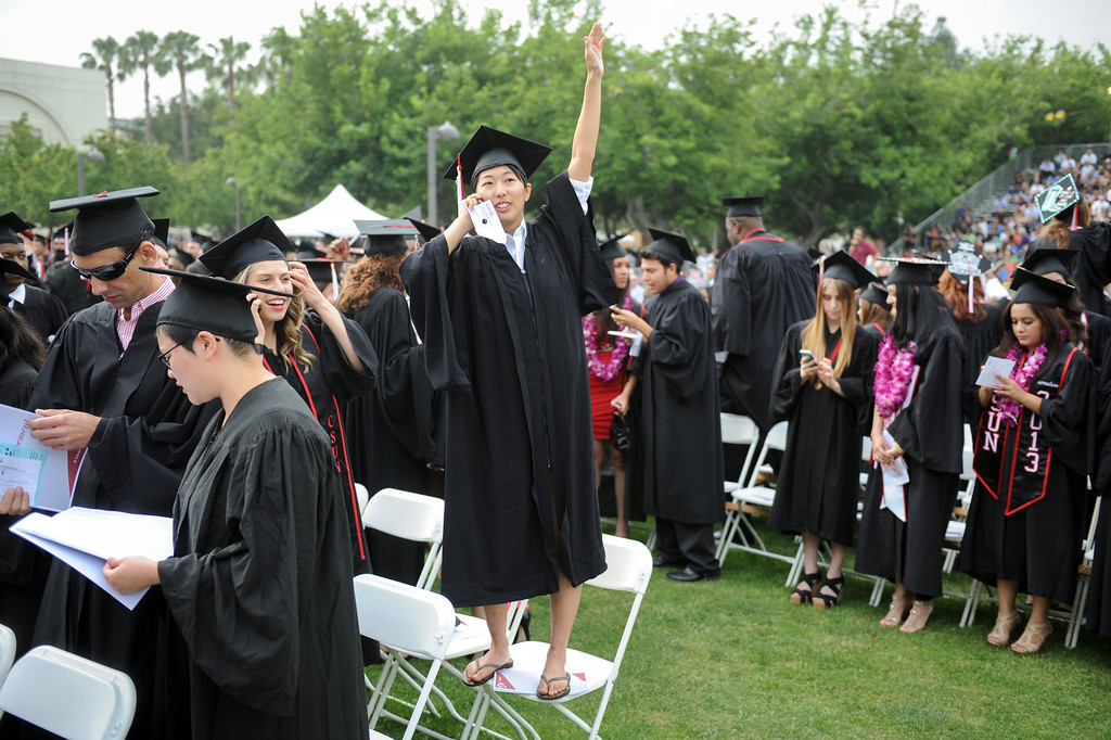 . Erika Yasuo stands on her chair while looking for relatives at the CSUN commencement ceremony, Tuesday, May 21, 2013. (Michael Owen Baker/L.A. Daily News)