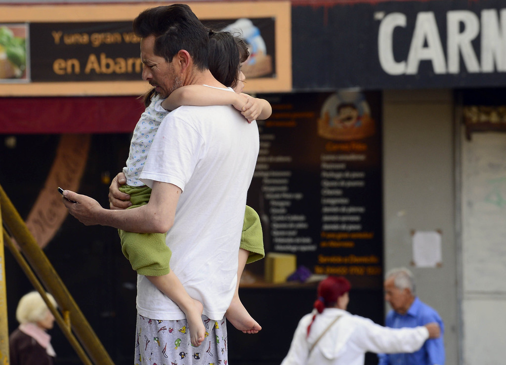 . A man holds his child after evacuating buildings after a strong earthquake rattled Mexico City on April 18 , 2014. A powerful 7.0-magnitude earthquake rattled Mexico City on Friday, swaying buildings, shattering windows and prompting people to rush into the street as power went out, authorities said. The National Seismology Service said the quake\'s epicenter was 31 kilometers (19 miles) northwest of Tecpan, in the southwestern state of Guerrero, near the Pacific resort of Acapulco. The US Geological Survey gave a higher measurement of 7.5-magnitude.   (ALFREDO ESTRELLA/AFP/Getty Images)
