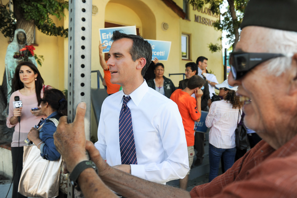 . Mayoral candidate Eric Garcetti talks with people in front of Dolores Mission Church in East Los Angeles during his Whistle Stop Tour of LA, Monday, May 20, 2013. Garcetti used the Expo, Gold and Red metro lines to greet voters in Los Angeles. (Michael Owen Baker/Staff Photographer)