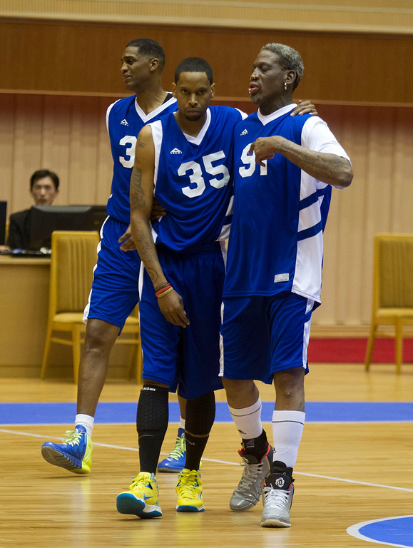 . Dennis Rodman, right, walks with fellow U.S. players Jerry Dupree, center, and Charles D. Smith during an exhibition basketball game with U.S. and North Korean players at an indoor stadium in Pyongyang, North Korea on Wednesday, Jan. 8, 2014. (AP Photo/Kim Kwang Hyon)