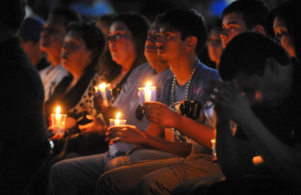 . Family members hold candles as students and members of the community gather in memory of Adrian Castro, 19, at El Monte High School Monday evening April 14, 2014. Castro was one of nine students killed in the bus crash in Orland, Calif. (Staff Photo by Keith Durflinger/San Gabriel Valley Tribune)