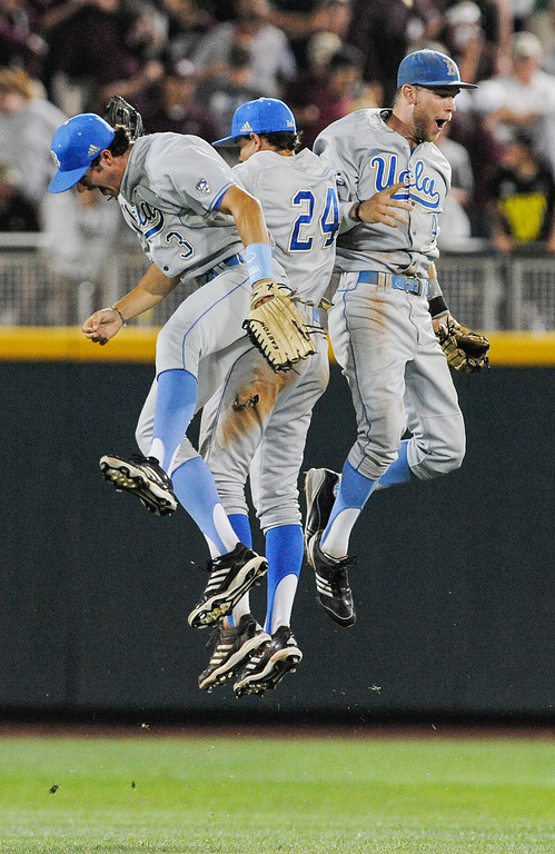 . UCLA outfielders from left: Christoph Bono, Brian Carroll and Eric Filia celebrate their 3-1 win over Mississippi State in Game 1 of the NCAA College World Series baseball best-of-three finals, Monday, June 24, 2013, in Omaha, Neb., (AP Photo/Eric Francis)