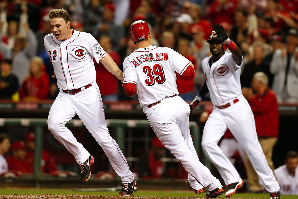 . CINCINNATI, OH - SEPTEMBER 23:  Devin Mesoraco #39 is congratulated by Jay Bruce #32 and Brandon Phillips #4 of the Cincinnati Reds after scoring the winning run during the 10th inning against the New York Mets at Great American Ball Park on September 23, 2013 in Cincinnati, Ohio. Cincinnati defeated New York 3-2 in 10 innings. (Photo by Kirk Irwin/Getty Images)