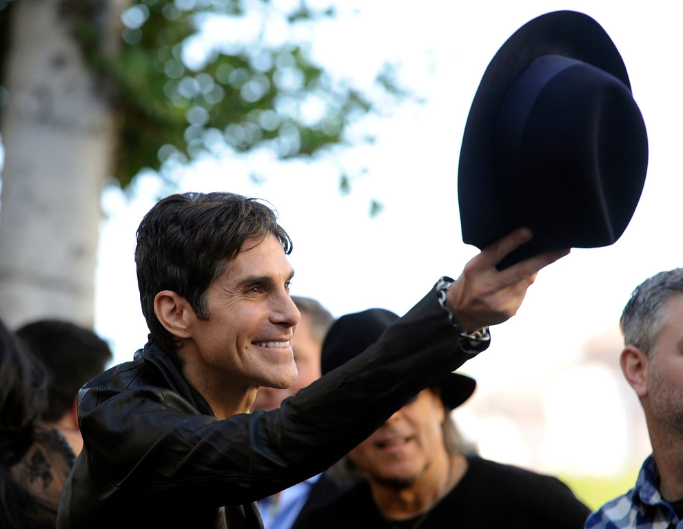. Perry Farrell, singer for the rock band Jane\'s Addiction, tips his hat to the crowd during a ceremony to award the band a star on the Hollywood Walk of Fame on Wednesday, Oct. 30, 2013, in Los Angeles. (Photo by Chris Pizzello/Invision/AP)