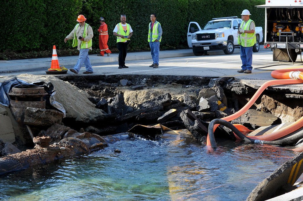 . Water continues to flow into a sinkhole from the broken water main on Sunset Boulevard near UCLA, Wednesday, July 30, 2014. (Photo by Michael Owen Baker/Los Angeles Daily News)