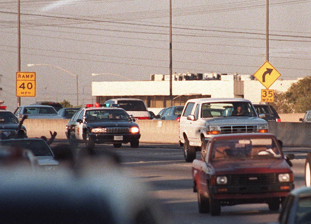 . Motorists wave as police cars pursue the Ford Bronco (white, R) driven by Al Cowlings, carrying fugitive murder suspect O.J. Simpson, on a 90-minute slow-speed car chase June 17, 1994 on the 405 freeway in Los Angeles, California. Simpson\'s friend Cowlings eventually drove Simpson home, with Simpson ducked under the back passenger seat, to Brentwood where he surrendered after a stand-off with police. (MIKE NELSON/AFP/Getty Images)