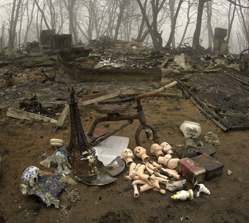 . A variety of salvaged items from a charred home are visible in the foreground as foggy weather envelops a charred home in Cuyamaca, Calif. Nov. 1, 2003. The home was one of 2,200 homes destroyed in the 275,000 acre Cedar fire east of San Diego. (AP Photo/Charlie Riedel)