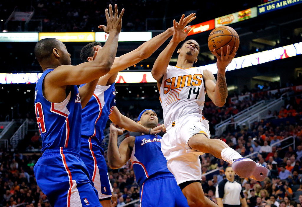 . Phoenix Suns guard Gerald Green (14) drives against Los Angeles Clippers forward Jared Dudley, rear; forward Hedo Turkoglu, center, of Turkey; and guard Willie Green, left, during the second half of an NBA basketball game, Wednesday, April 2, 2014, in Phoenix. The Clippers won 112-108. (AP Photo/Matt York)