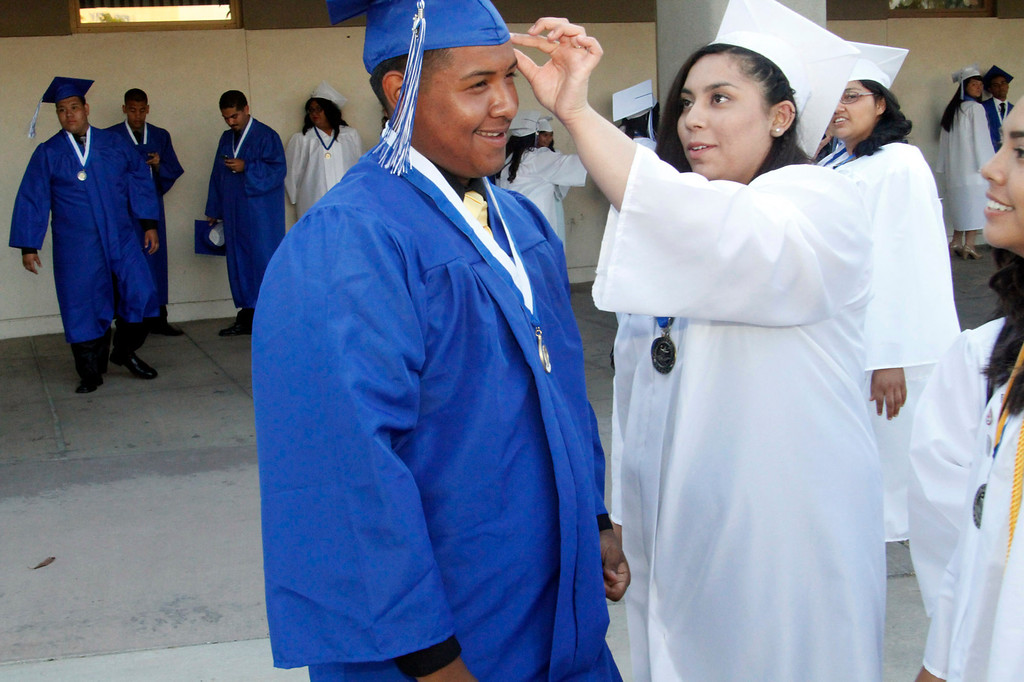 . Paulina Pulido, right, helps David Pedraza with his cap, before the El Monte High School Class of 2014 Commencement Ceremony, at El Monte High School\'s Football Stadium in El Monte, CA., Wednesday, June 11, 2014.  (Photo by James Carbone for the San Gabriel Valley Tribune)