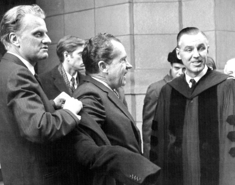 . Evangelist Billy Graham, left, helps President-elect Richard Nixon with his overcoat after they attended services at 5th Avenue Presbyterian Church, in New York, on Jan. 5, 1969.  Dr. Bryant M. Kirkland, right, minister of the church, talks to Nixon. (AP Photo)