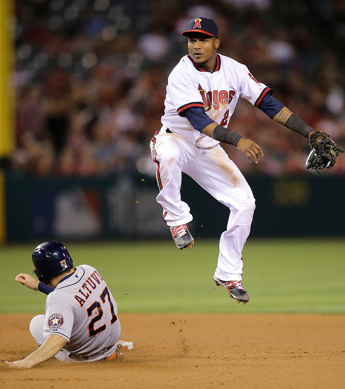. Los Angeles Angels\' Erick Aybar, top, throws to first base after forcing out Houston Astros\' Jose Altuve during the seventh inning of a baseball game on Friday, Aug. 16, 2013, in Anaheim, Calif. Houston Astros\' Jason Castro was out at first. (AP Photo/Jae C. Hong)