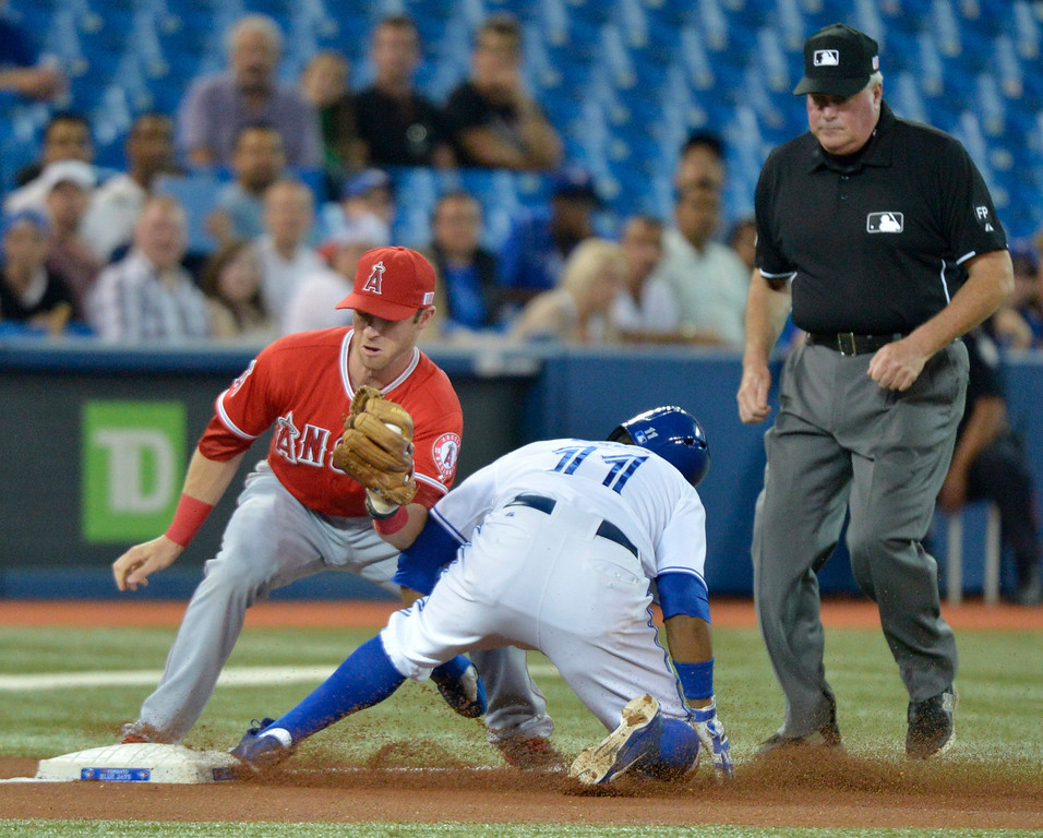 . Toronto Blue Jays\' Rajai Davis, center, steals third as Los Angeles Angels\' Andrew Romine, left, looks on during first-inning AL baseball game action in Toronto, Wednesday, Sept. 11, 2013. (AP Photo/The Canadian Press, Nathan Denette)