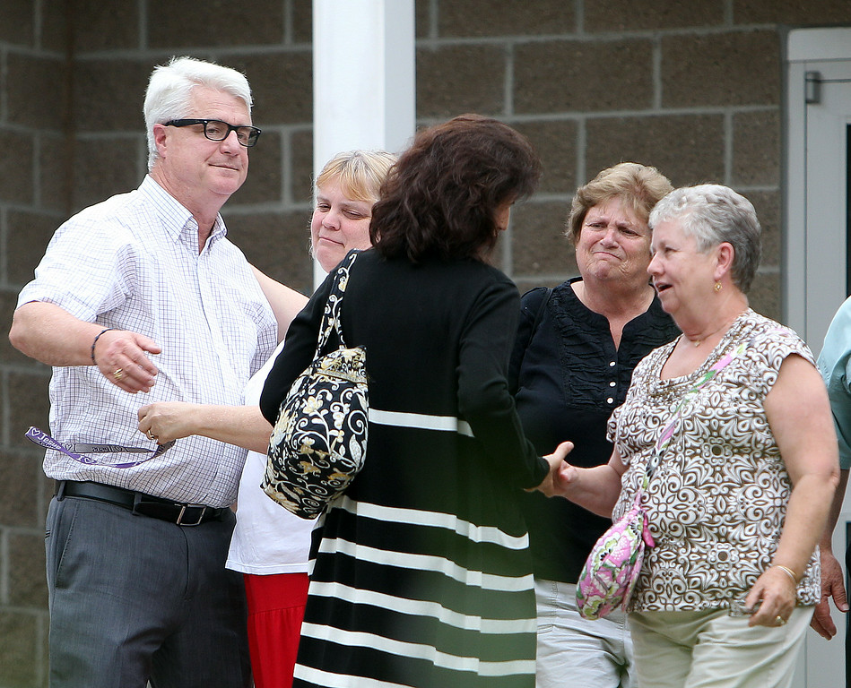 . John Foley, far left, and his wife Diane, back to camera, talk with supporters, Thursday, July 25, 2013 in Rochester, N.H. after a  moment of silence for James Foley,  their missing son. Foley, 39, was last seen Nov. 22 in northwest Syria. He was contributing videos to Agence France-Press for the media company GlobalPost, which has said Foley was likely abducted by a pro-Syrian government military group. Investigators believe he is being held with one or more Western journalists in a detention facility near Damascus.(AP Photo/Jim Cole)