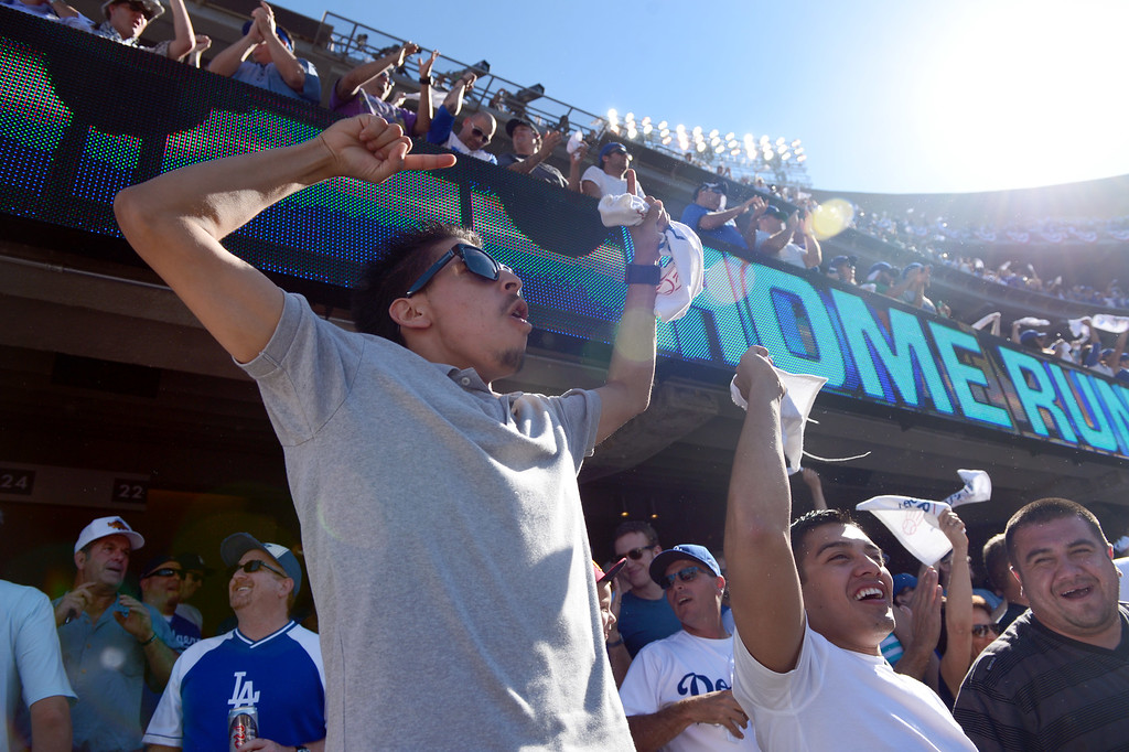 . Fans celebrate Los Angeles Dodgers\' Carl Crawford\'s home run to right field in the fifth during game 5 of the NLCS at Dodger Stadium Wednesday, October 16, 2013. (Photo by Sarah Reingewirtz/Los Angeles Daily News)