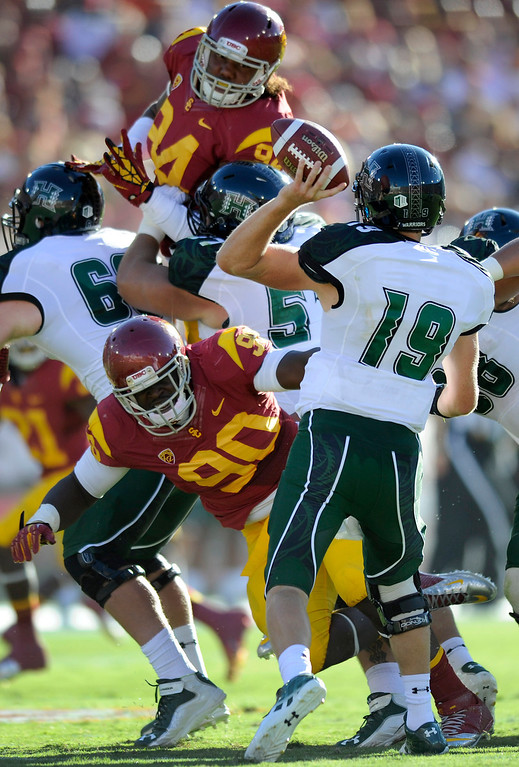 . Hawaii QB Sean Schroeder has to pass over USC linemen George Uko (#90) and Leonard Williams, top, Saturday, September 1, 2012, at the Los Angeles Memorial Coliseum. (Michael Owen Baker/L.A. Daily News)