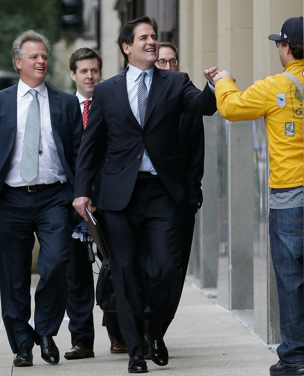 . Billionaire Dallas Mavericks NBA basketball team owner Mark Cuban gets a fist bump as he walks with his legal team to the federal courthouse after a break in his insider trading trial in Dallas, Wednesday, Oct. 16, 2013. Jurors say billionaire Mark Cuban did not commit insider-trading when he sold his shares in an Internet company in 2004 after learning of a development that would dilute the value of his investment. The jury in federal court found that the SEC failed to prove several key elements of its case, including that Cuban traded on nonpublic information. (AP Photo/LM Otero)