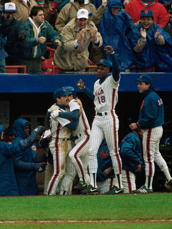 . Darryl Strawberry (18) of the New York Mets celebrates as teammates Howard Johnson, left, and Wally Backman hug on the dugout steps after Backman scored to tie the game with the Los Angeles Dodgers, Saturday, Oct. 8, 1988, New York. After the comeback, the Mets went on to win to take a 2-1 lead in the playoffs. (AP Photo/Richard Drew)
