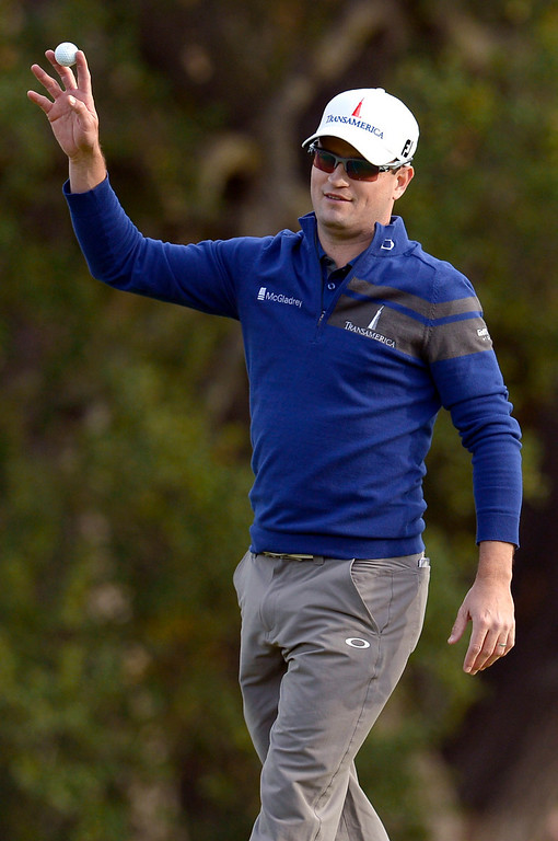. Zach Johnson raises his ball after chipping in from the drop zone on the 18th hole during the final round of the Northwestern Mutual World Challenge golf tournament at Sherwood Country Club, Sunday December 8, 2013, in Thousand Oaks, Calif.   Johnson would go on to beat Tiger Woods on a playoff hole.(Andy Holzman/Los Angeles Daily News)